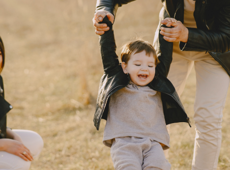 Boy laughing with parents.