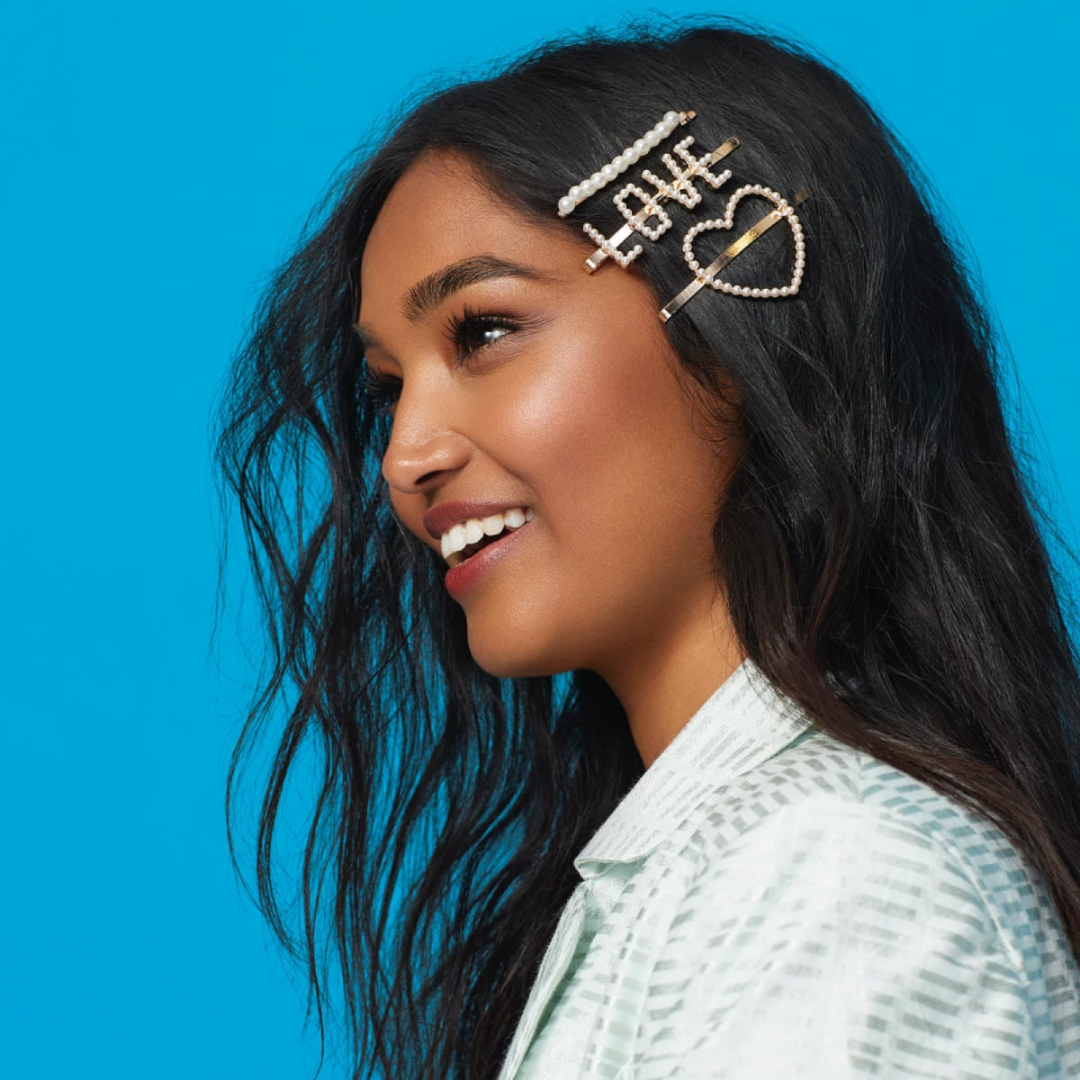Girl wearing hair clips with a heart, love word and pearls from Aldo