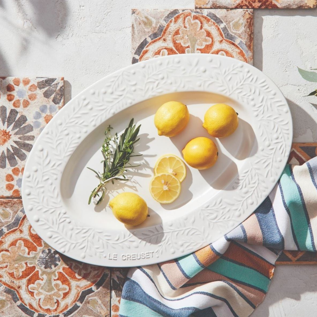 Oval white dinner serving platter from Le Creuset with lemons on top.