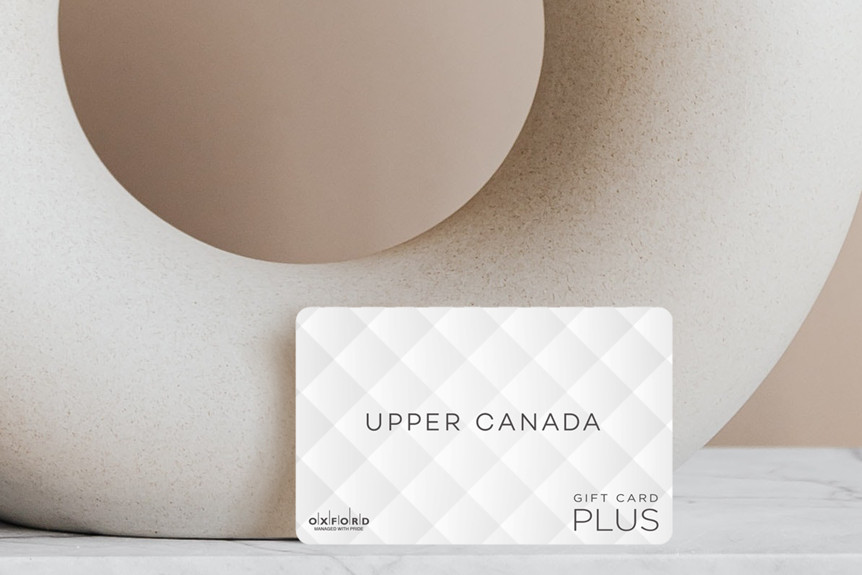 Upper Canada mall white quilted gift card leaning against beige circular vase.