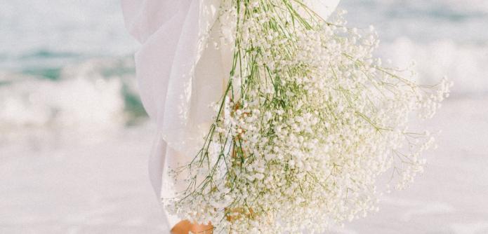 Bride holding a bouquet along the beach