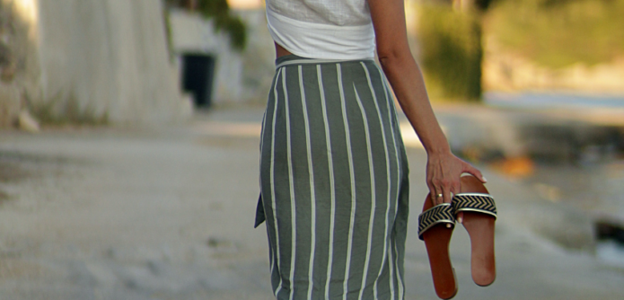 Girl walking away holding a pair of sandals and sunhat, wearing a green striped skirt and white tee.