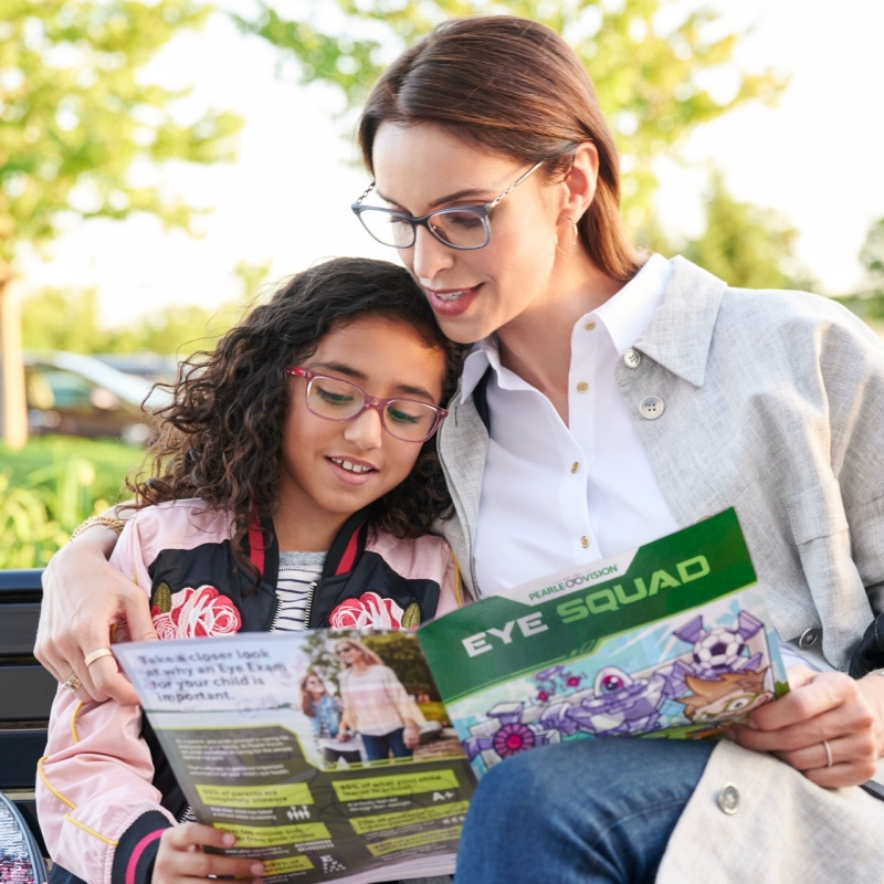Mother and daughter reading magazine